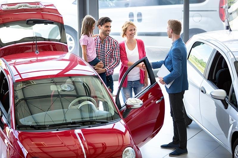 Family looking at cars with salesman at dealership