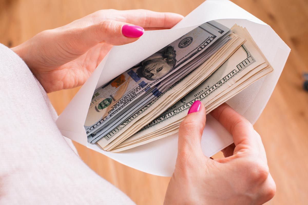 Woman holding envelope with cash inside