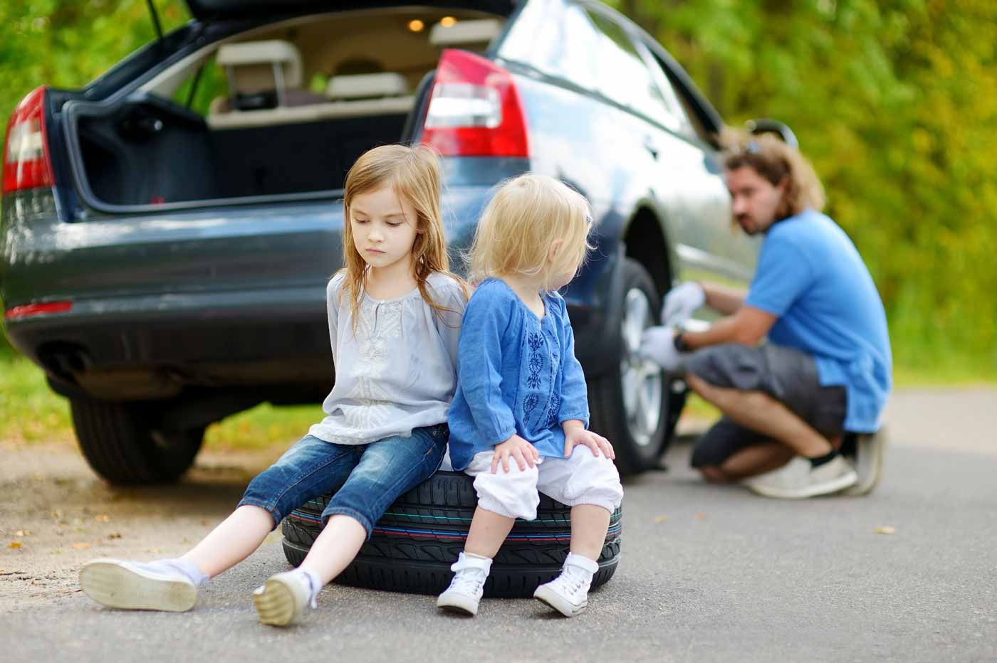 Father works on car on side of the road while two daughters sit sadly on tire