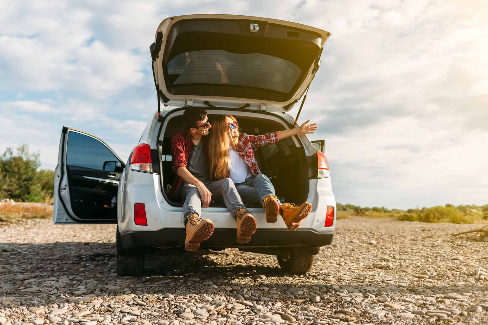 Couple sitting in open back of car with open hatch on rocky road