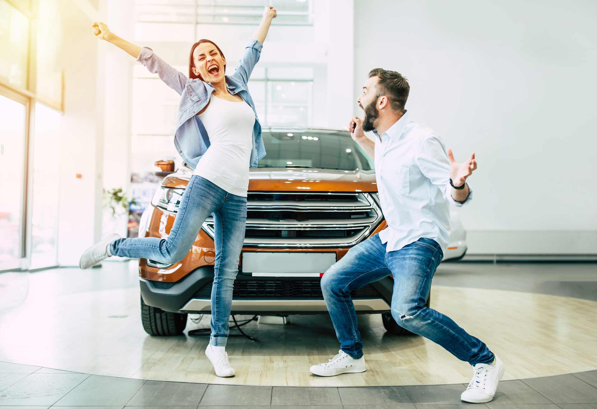 Woman and man celebrating getting a new car