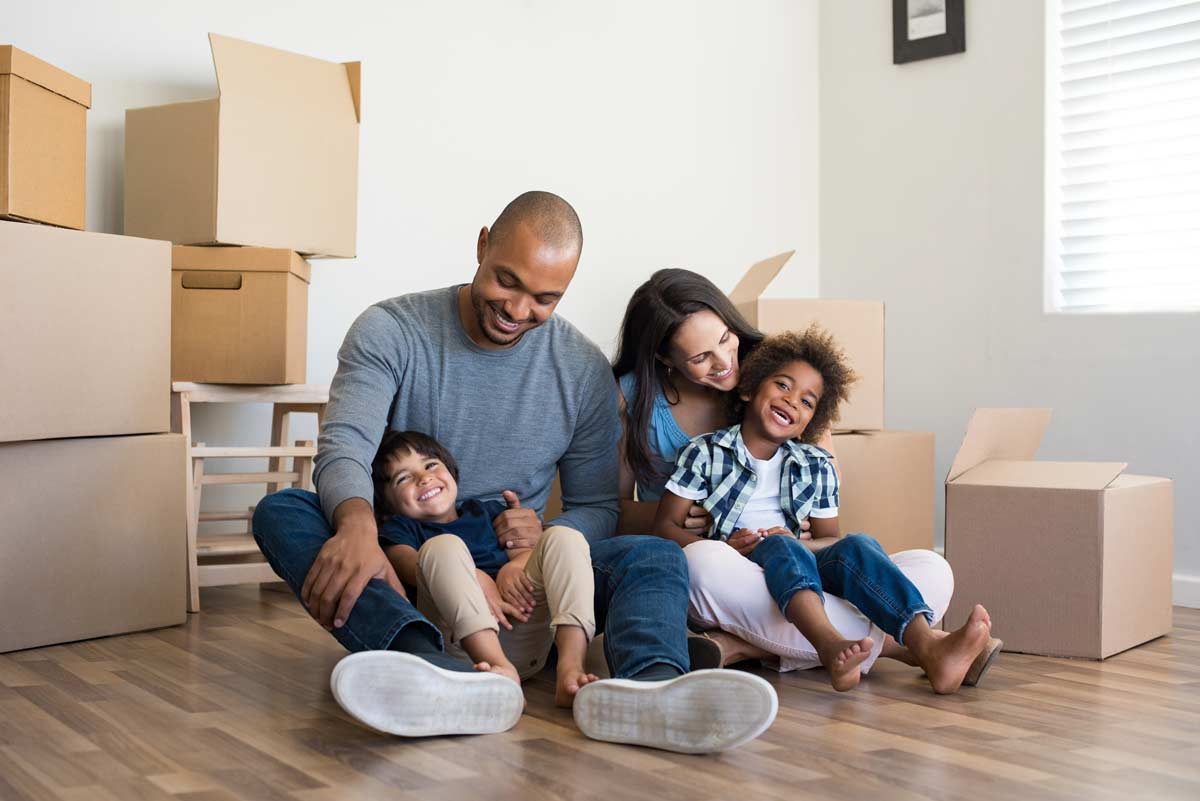 Parents and kids sitting together surrounded by moving boxes