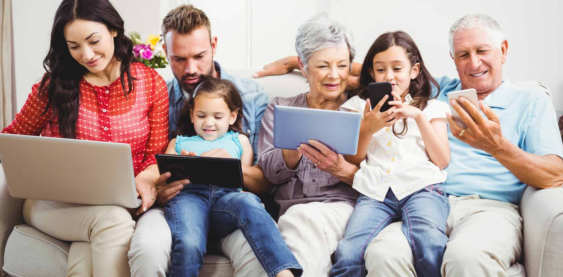 Multi-generational family sitting and interacting together on a variety of devices