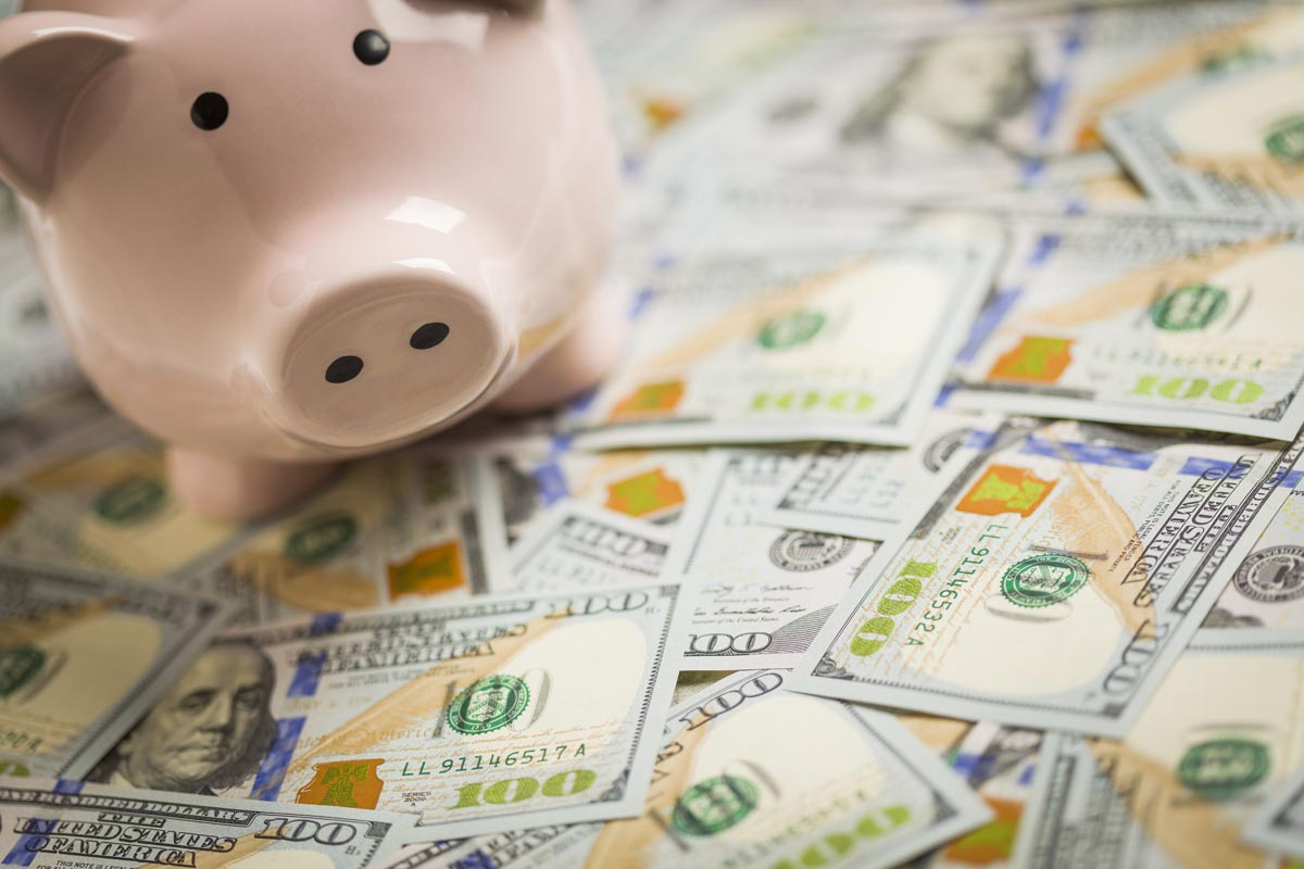 Piggy bank sitting on scattered $100 bills