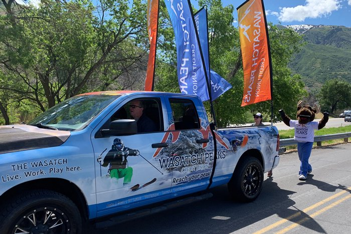 Wasatch Peaks truck with flags and MONEY MOO$E in a parade