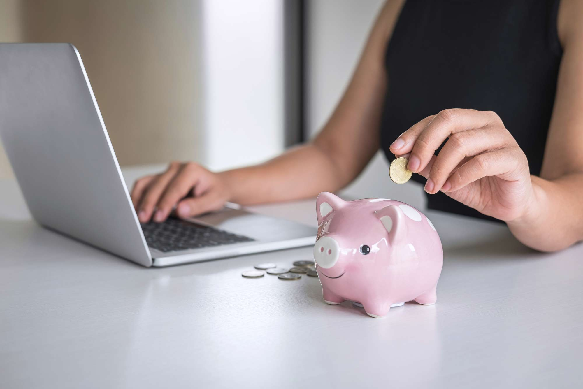 Person typing on computer and putting coins into a piggy bank