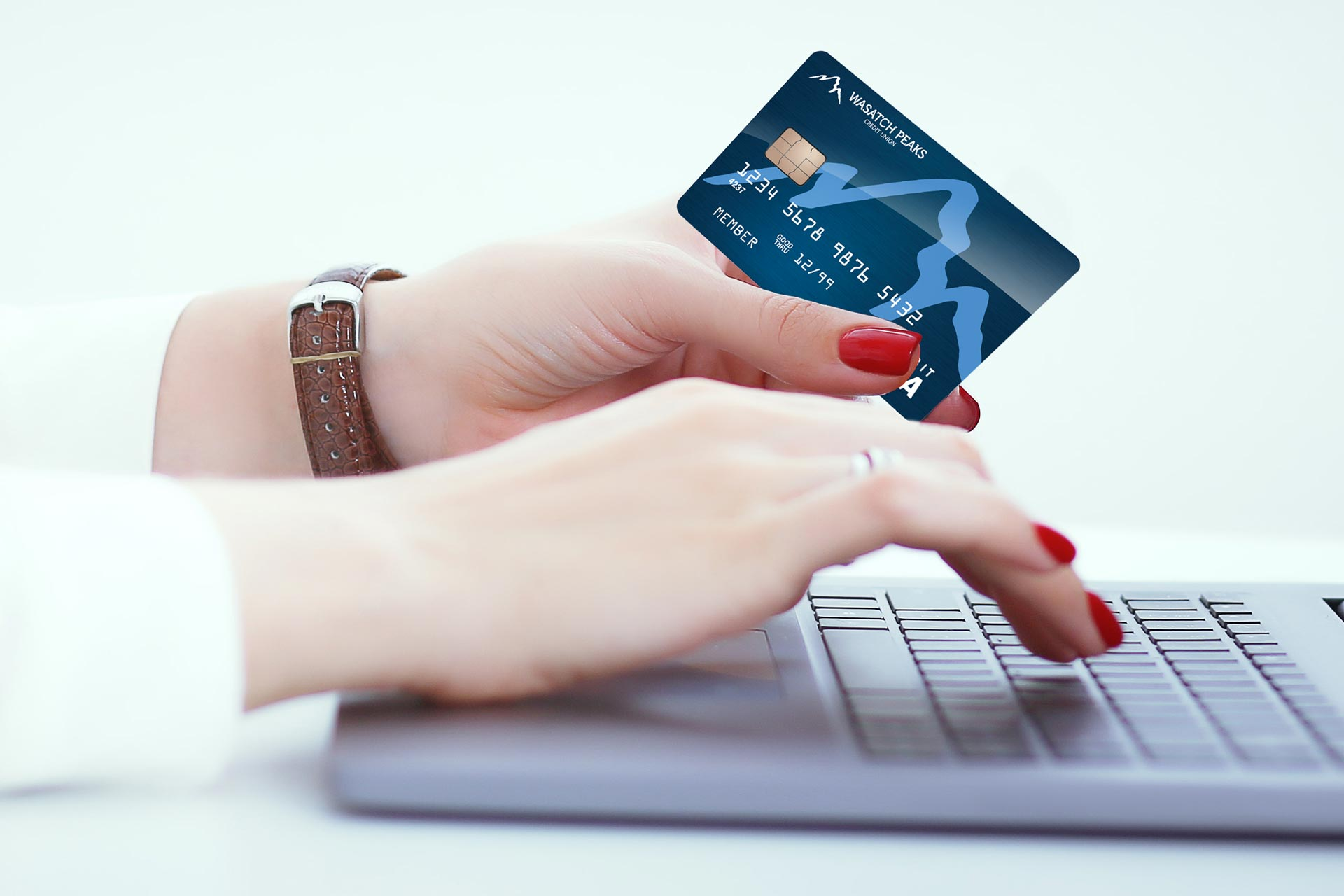 Woman's hands typing on laptop while holding a Wasatch Peaks debit card