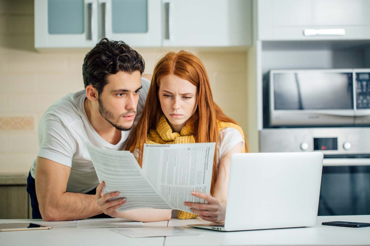 Couple looking focused at papers and at laptop in kitchen