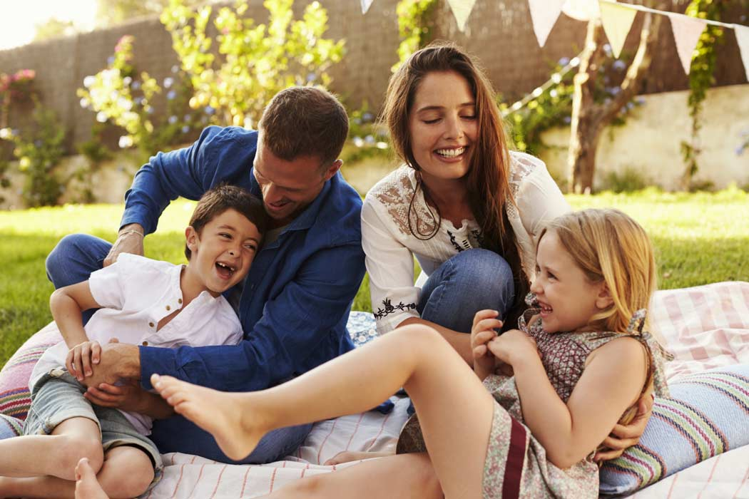 Family laughing together in back yard
