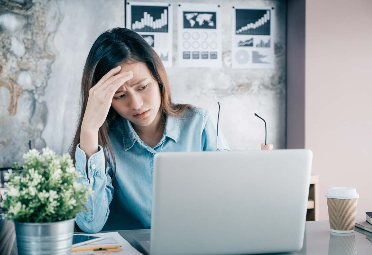 Worried young woman looking at laptop