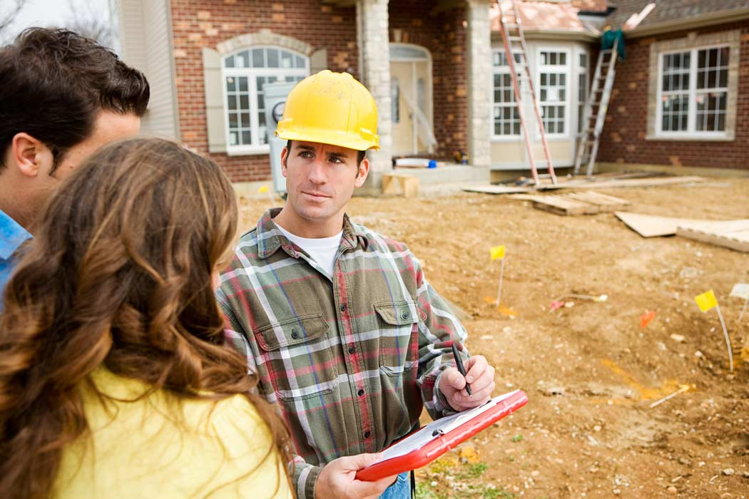 repair contractor talking with couple in front of house