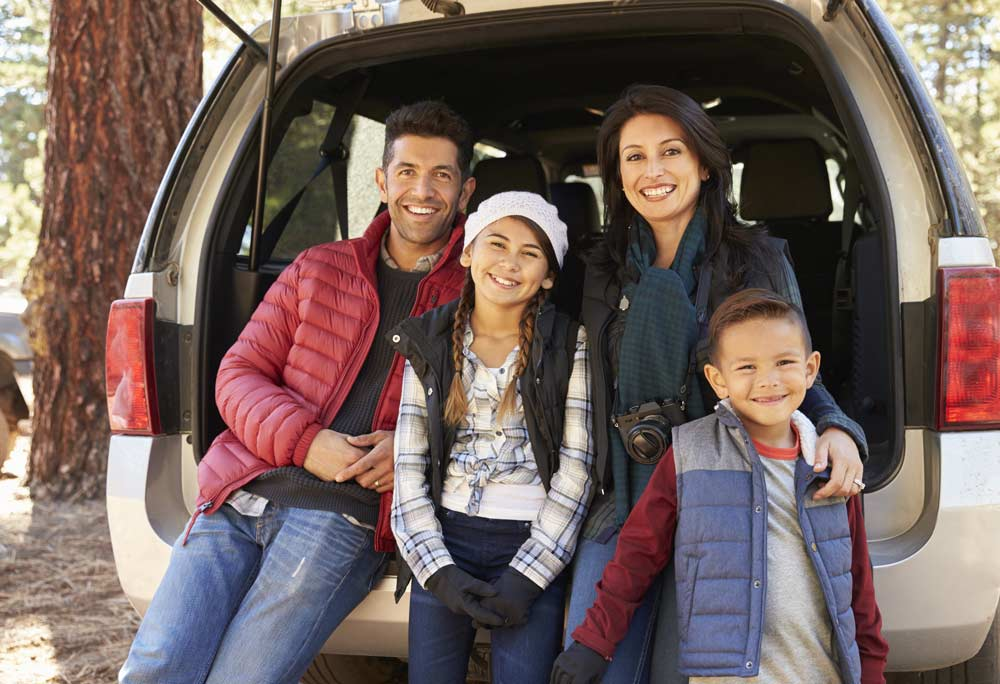 Family standing together behind SUV