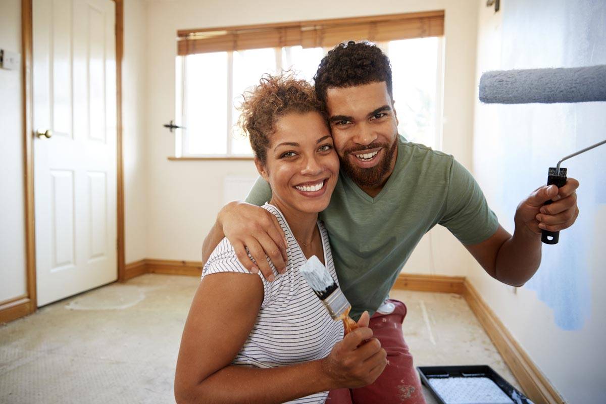 Couple smiling and holding paint brush and roller