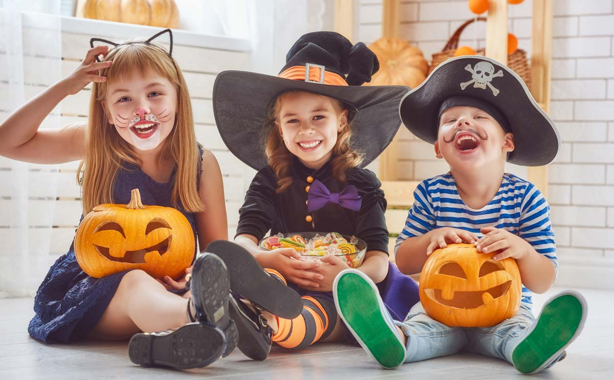 Kids in Halloween costumes with candy and pumpkins