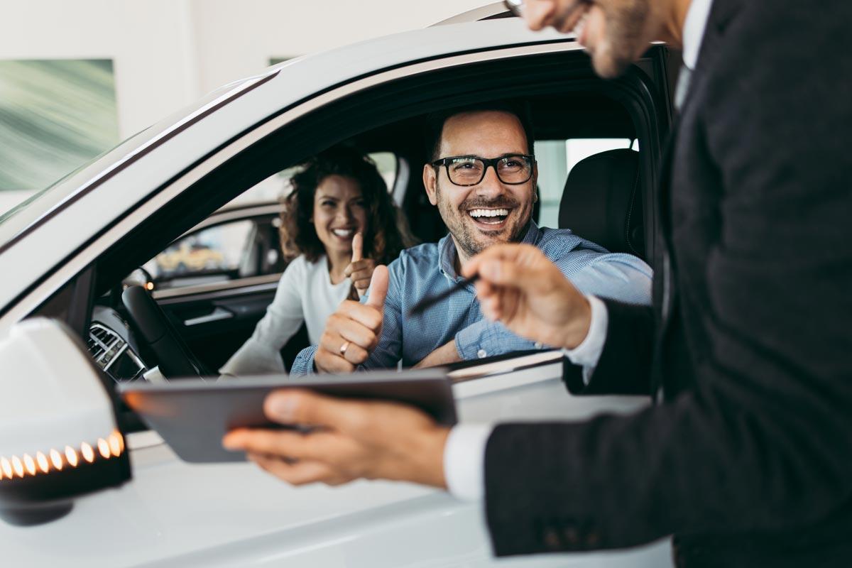 Man and woman inside car talking to salesman