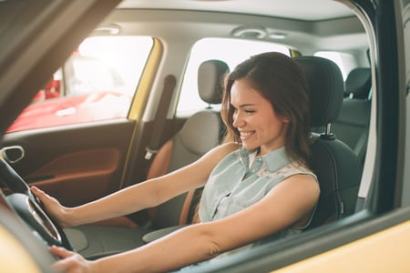 woman smiling in her new car