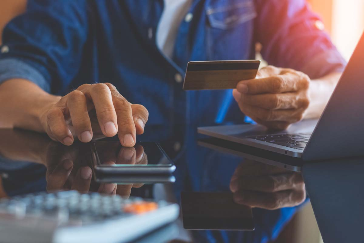 Man looking at smartphone and debit card