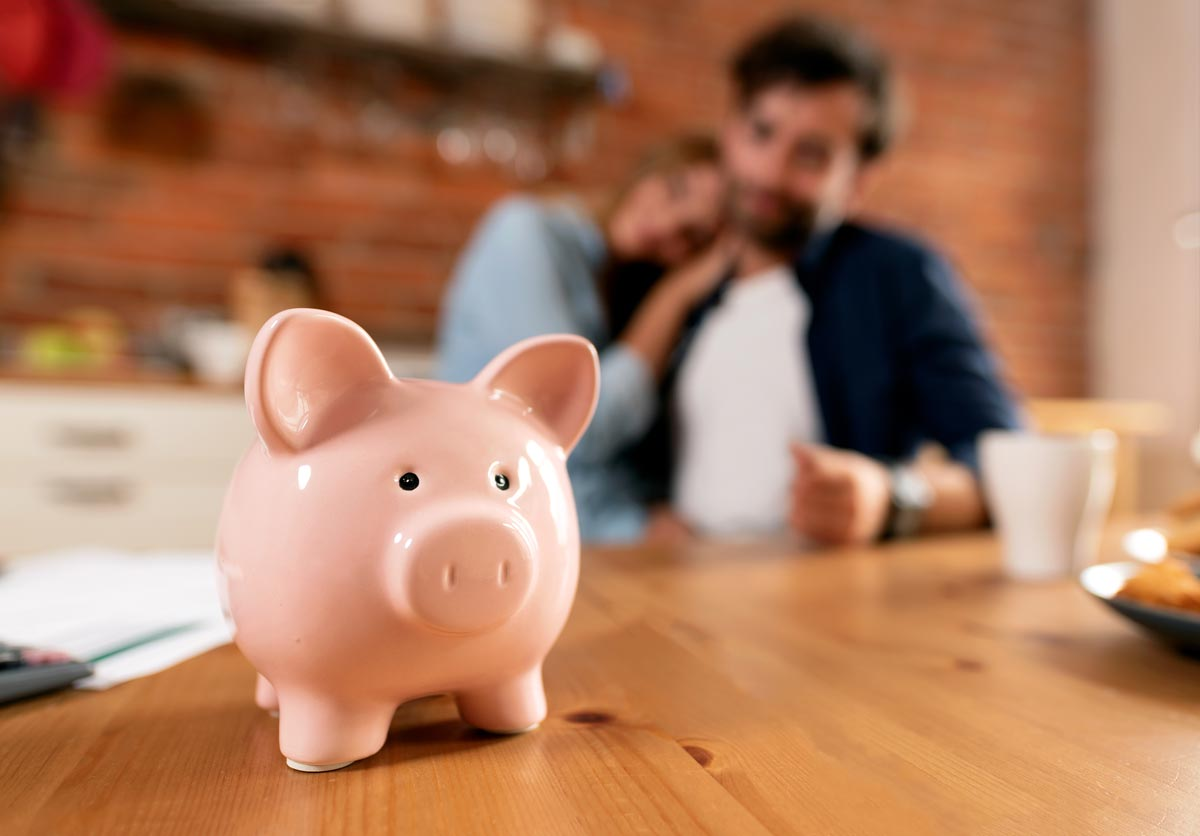 piggy bank on table in front of happy couple