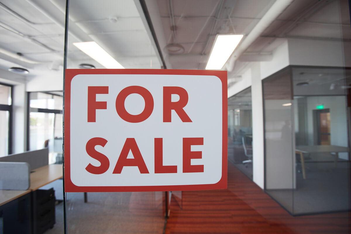 a for sale sign in the window of a contemporary office building