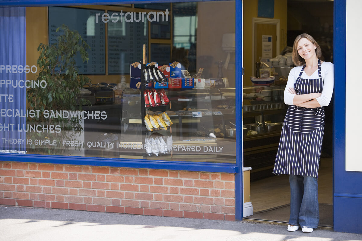 a small business owner in an apron standing in the doorway of her restaurant