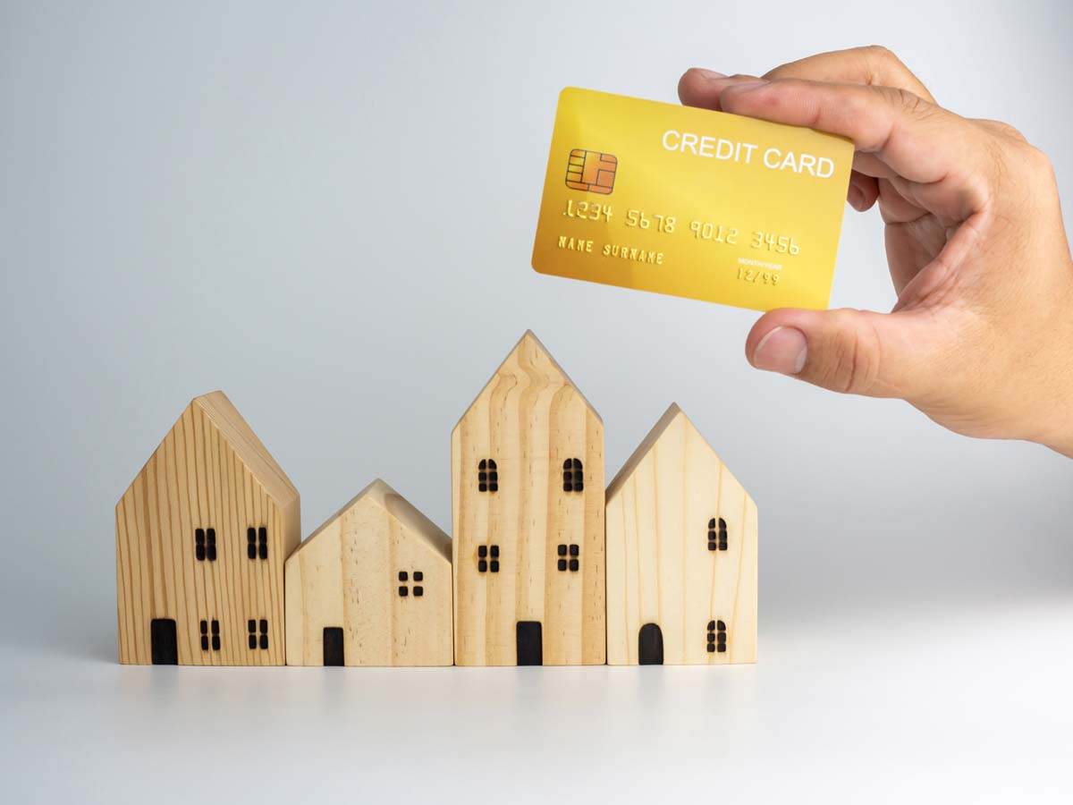 holding credit card over a house
