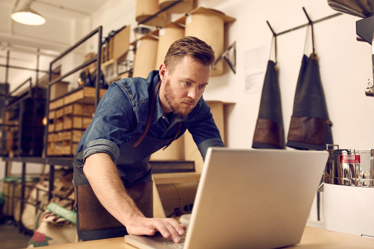 man on laptop in workshop